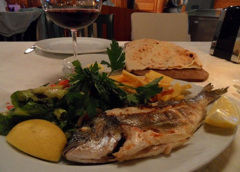 Color photo of a whole grilled fish - Sea Bream - dinner.