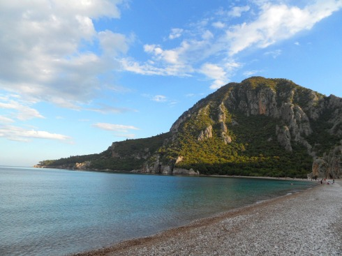 Color photo of beachscape in Chirali.  Mountains landing into the Mediterranean Sea.