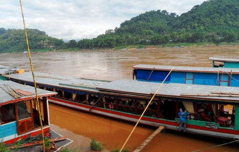 Color photo of a long boat on the Mekong River