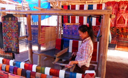 Women weaving a silk scarf in her street stall